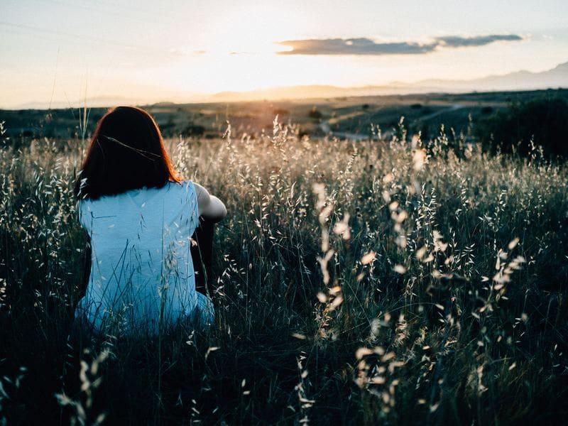 Frau sitzt auf Wiese und schaut in die Ferne